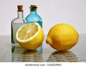 Still life with two ripe juicy lemons and cold fresh lemonade in two small vintage glass botlles against a high key background with space for your text. Selective and soft focus.