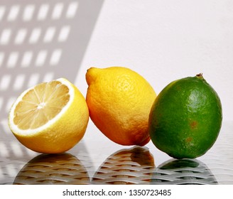 Still life with two ripe juicy lemons and green lime against a high key background with space for your text. Selective and soft focus.