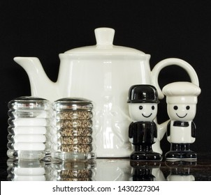 Still life with two sets of salt and pepper shakers, one modern and a set of collectable, vintage Homepride flour figures known as Fred. White teapot in the background and a black backdrop.
