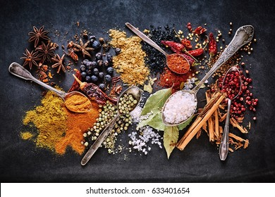 Still life of a variety of dried culinary spices for Asian and Oriental cuisine with curcuma, star anise, salt, cinnamon, peppercorns, acai, bay leaves, chili and cayenne pepper viewed from overhead