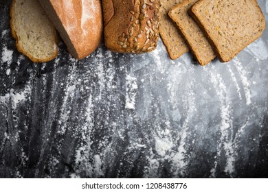 still life of various breads on a dark background with flour