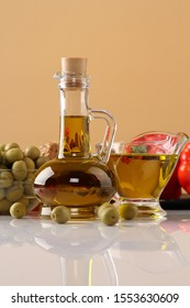 Still life with a vase of olives, a jug of olive oil and red pepper on a beige background