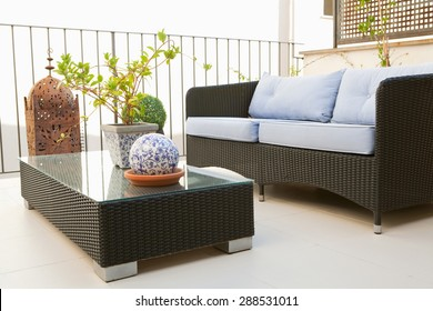 Still life view of a home outdoors terrace balcony relaxing and lounging area with wicker coffee table and sofa, in an elegant house, exterior. Summer home living, empty space, aspirational lifestyle.