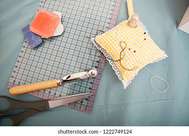 Still life view of tailor tools on working table, indoors. Seemstress utensils, chalk, ruller, pins, cushion, fabric. Colorful trade objects, textiles and fashion industry inspiration.