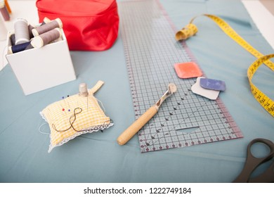 Still life view of tailor tools on working table, indoors. Seemstress utensils, chalk, ruller, measuring tape, threads, pins, cushion, fabric. Colorful trade objects, textiles and fashion.