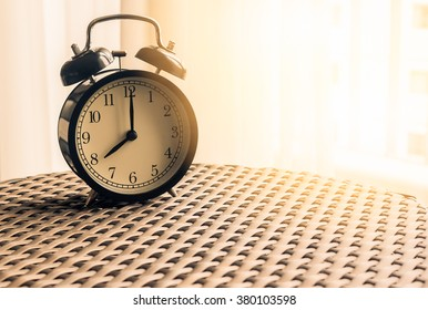 Still life , vintage alarm clock on weave table with sunlight ( alarm clock show 8 o`clock )
