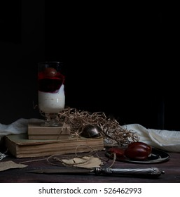 still life, vintage. fresh dairy dessert with plums, old books on a wooden table drape