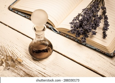 Still life vintage picture, old perfume bottle and a bunch of dried lavender on a journal.