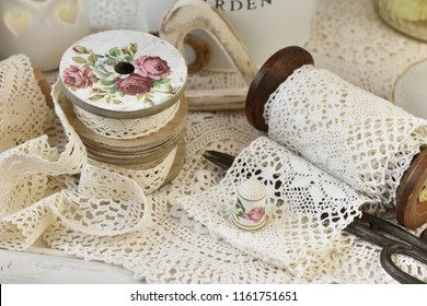 still life with vintage style cotton lace trim spools and sewing accessories