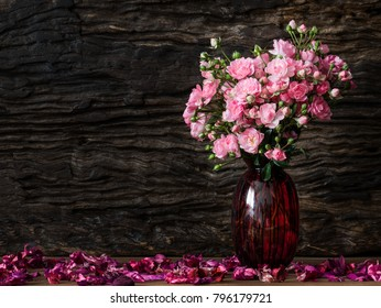 Still life visual art of pink roses arrangement in red glass vase on wooden slap with dry flowers falling round and old wooden back drop