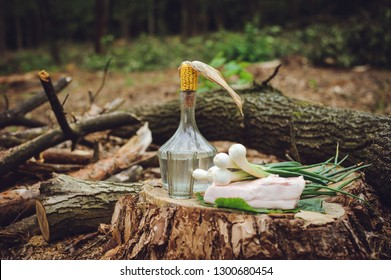 Still life with vodka on a stump. National lunch of Ukrainian loggers. A bottle of moonshine, clogged with a corn cob, fresh salty salo and green onions.