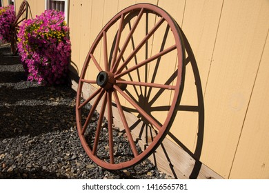 Still life of wagon wheel and flowers against a building