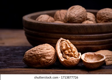 still life with Walnut kernels and whole walnuts on rustic old wooden table.
