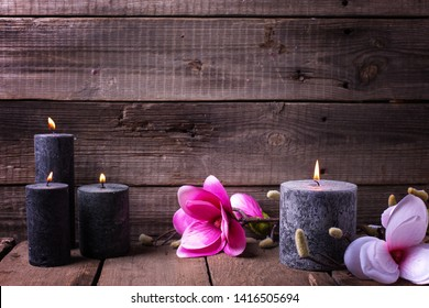 Still life wellness  layout. Black burning candles  and pink magnolia flowers on  wooden rustic  background.  Selective focus. Place for text.