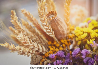 Still life with wheat ears, dry poppy head, yellow and violet wildflowers. Toned image.