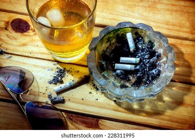 Still life with whiskey and cigarettes on wooden table