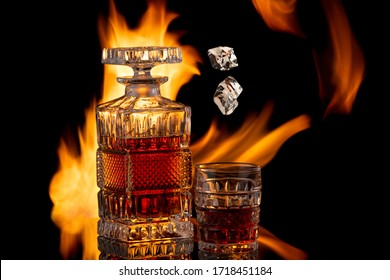 Still life with whiskey and ice cubes on the background of fire, brandy in a glass and flames