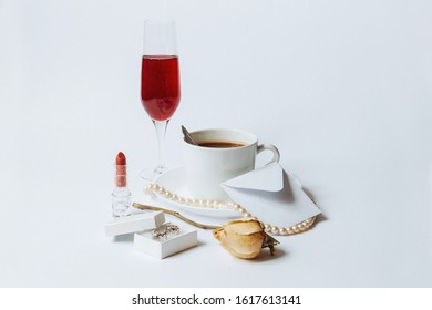A still life with a white ceramic cup of coffee, a faded rose, a coral necklace, a lipstick, a box with the silver earrings, a white envelop, and the glass of champagne isolated on a white background.
