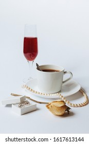 A still life with a white ceramic cup of coffee, a faded rose, a coral necklace, a little white box with the silver earrings, and the glass of champagne isolated on a white background.