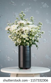 still life of white Chrysanthemum flowers and white small Daisy flowers arrangement in black vase on small round table with silver background