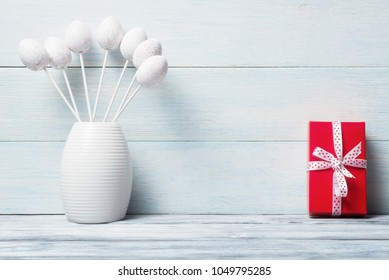 Still life with white decorative eggs and red gift box over wooden background.