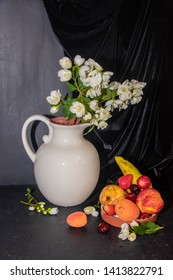 Still life, In a white jug there are branches of jasmine, and next to it are fruits. Strawberries, pears, bananas, apricots. From behind hanging velvetnakkani. Dark background.