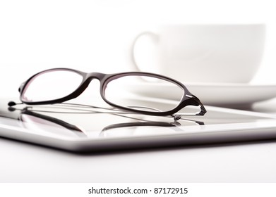 Still life with white tablet, coffee cup and glasses on a white table