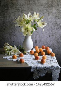 Still life: a white vase with lilies & one white lily sprig, sixteen apricots on an iron plate & a on wooden table covered with a white knitted crocheted tablecloth & on a background of an old wall