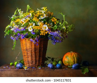 Still life with wild flowers in a basket and pumpkin