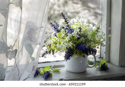 Still life with wildflowers in a white mug on a white window in a country house.