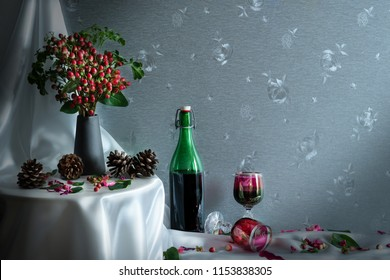 Still life of wine bottle and two winw glasses with a vase of red berry on round table and pine seed on white cover cloth