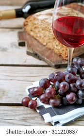 Still life of wine and bread on rustic wooden background
