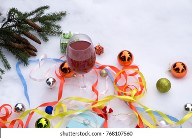 Still life wine, gifts and Christmas tree ornaments in the snow.