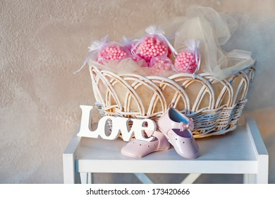 Still life with wooden love letters, baby's shoes and wicker basket
