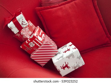 Still life of wrapped Christmas gifts sitting on a red chair