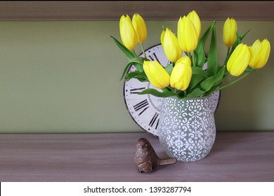 Still life. Yellow flowers are in a white vase. On the background there is a vintage round clock. Nearby is the golden bird.