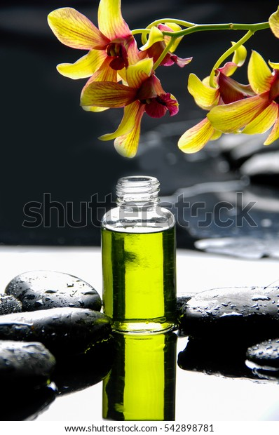 still life with yellow orchid ,massage oil and wet black stones
