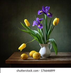 Still life with yellow tulips, irises and lemons