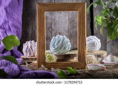 Still life with zephyr or meringue with a wooden frame. Homemade sweets.