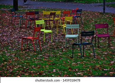 Still of numerous colorful chairs standing in disarray at a garden between green grass and fallen brown leaves