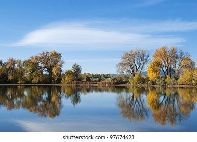 Still pond or lake on the Colorado prairie in early autumn with golden autumn colors