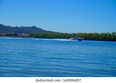 Still river water on a sunny day with a boat going fast at Viana do Castelo, Portugal