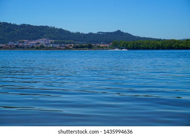 Still river water on a sunny day with a water jet going fast at Viana do Castelo, Portugal