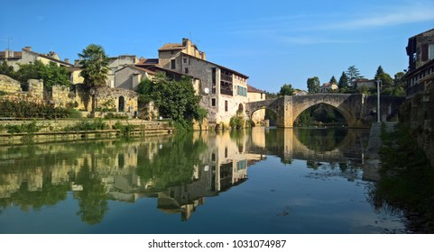 A still summer day in the traditional French town of Nérac, reflected in the calm waters of the river Baise