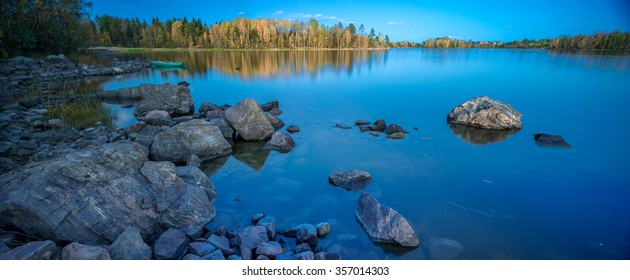 Still water of Ladoga lake with rocks on the foreground and green boat and islands covered with birch and pine forest at sunset, Republic of Karelia, Russian North-West