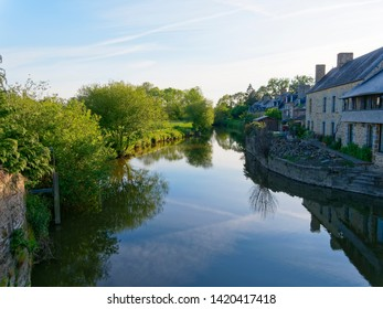 The still water of the River Selune reflects the evening sky in the town of Ducey-les-Cheris, Normandy, France. Insects fly above the surface of the river