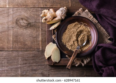 Stillife with ground ginger and fresh ginger pieces over wooden background. Top view, Copyspace