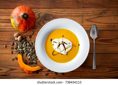 Stillife of pumpkin soup, decorated with pumpkin and seeds