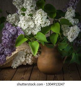 Still-life with a bouquet of lilacs and a straw hat, close-up
