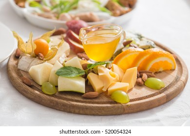 Still-life cheese platter with nuts and grapes